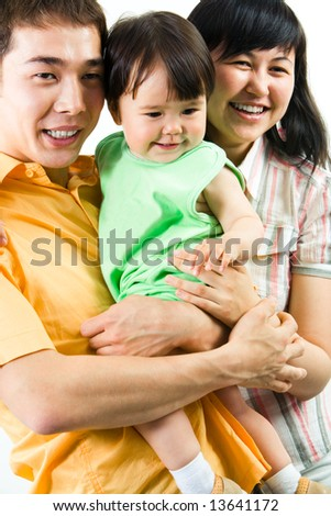 Photo of father and mother keeping their small daughter - stock photo