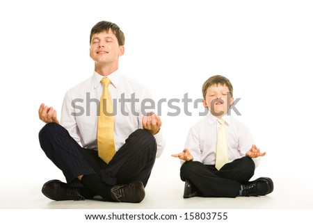 Photo of father and son sitting in pose of lotus with their eyes closed and meditating - stock photo