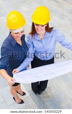 Photo of female constructors holding the project in the hands while smiling