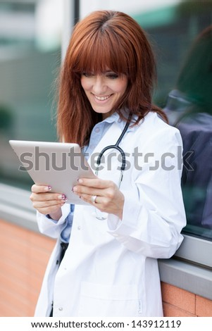 Photo of female doctor looking at the tablet pc while smiling