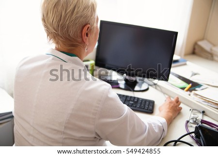 photo of female doctor using desktop PC in clinic