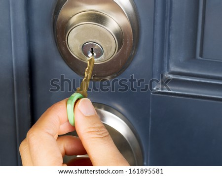 Photo of female hand putting house key into front door lock of house - stock photo