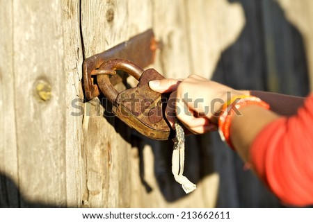 Photo of female hand putting house key into front old door lock of house - stock photo