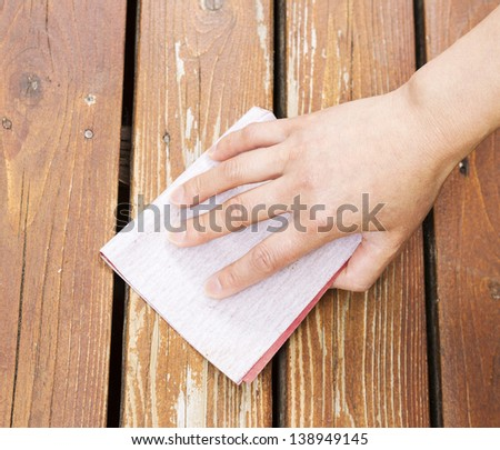 Photo of female hand with sand paper on natural faded cedar wood deck - stock photo