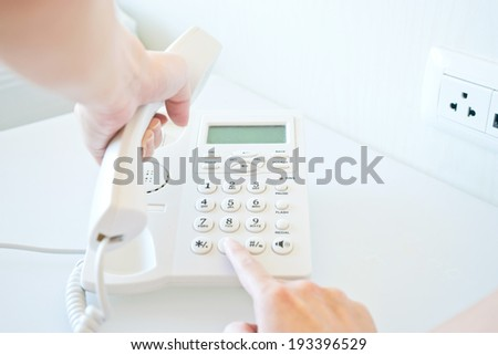 Photo of female hands dialing on white telephone - stock photo