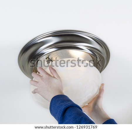 Photo of female hands installing glass lid over new light bulbs with white ceiling in background - stock photo
