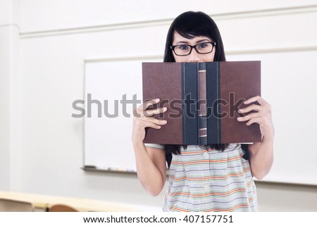 Photo of female high school student wearing glasses and standing in the classroom while holding a book and looking at the camera - stock photo