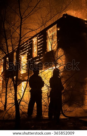 Photo of Firemans Trying to Safe House on Fire. Firefighter Emergency Extinguish Water on Big Old Wooden House on Fire - stock photo