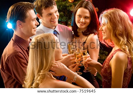Photo of five smiling friends touching their glasses with each other at christmas - stock photo