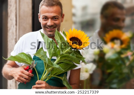 Photo of florist with a sunflower in his hands next to his shop - stock photo