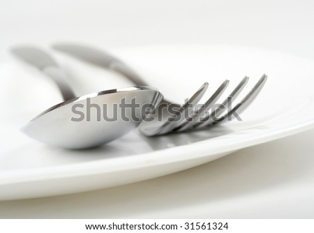 Photo of fork and spoon on plate - stock photo