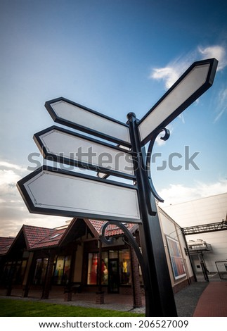 Photo of four blank street signs on intersection - stock photo