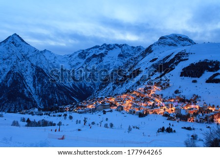 Photo of France ski resort Les Deux Alpes at the evening. You can see a part of resort with many mountains around it.