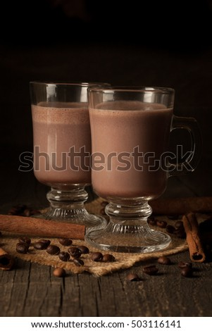 Photo of fresh Made Chocolate Banana Smoothie on a wooden table with coffee and spices. Selective focus. Milkshake. Protein diet. Healthy food concept. Drink, coffee beans, chocolate, cinnamon, anise.