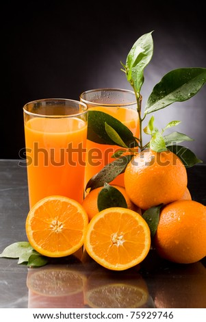 photo of fresh orange juice with water drops and green leaves - stock photo