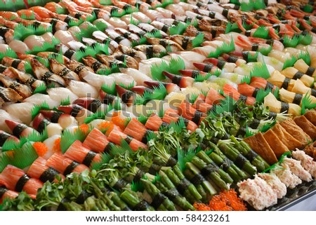 Photo of fresh sushi platter with a lot of variety. Selective focus on middle of the platter. - stock photo