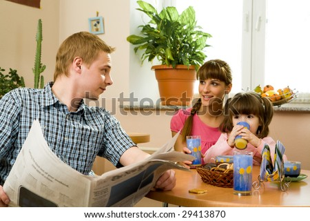 Photo of friendly woman speaking to her husband in the kitchen while he reading paper and their daughter drinking juice - stock photo
