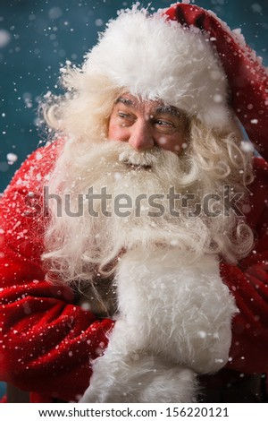 Photo of frozen Santa Claus outdoors in snowfall at north pole at night - stock photo