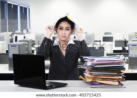 Photo of frustrated female entrepreneur put a paperwork on her head with a pile of document and laptop on desk in office - stock photo