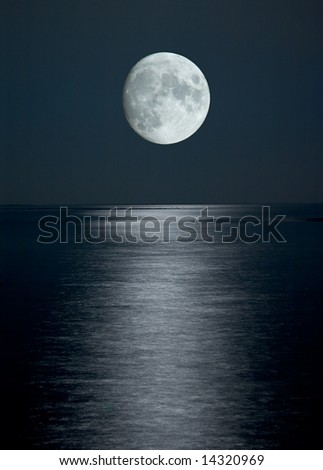 Photo of full moon in black sky above the sea with reflection - stock photo