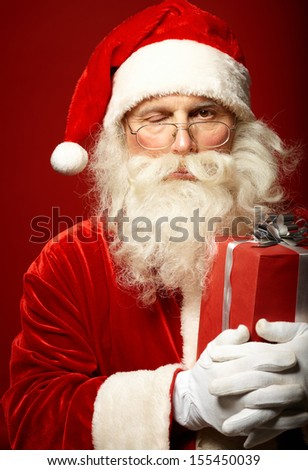 Photo of funny Santa Claus with one eye closed looking at camera