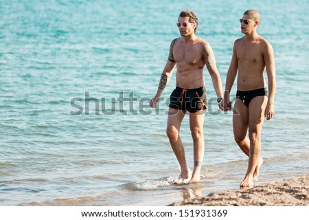 Photo of gay couple at the beach walking through the water while holding hand   - stock photo