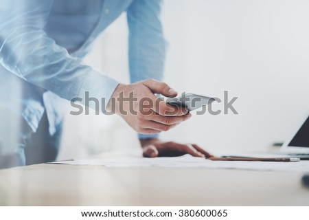 Photo of generic design smart phone holding in businessman hands. Blurred background. Horizontal mockup - stock photo