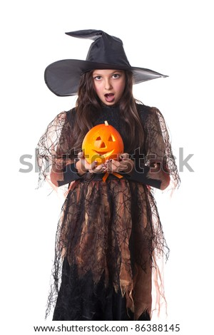 Photo of girl in halloween costume with a pumpkin on hands and looking surprised - stock photo