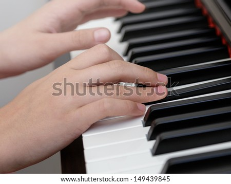 photo of girls hands playing on piano, shallow depth of field