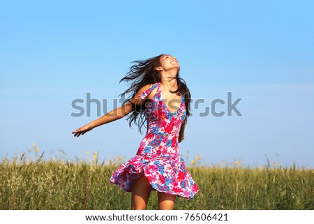 Photo of glad girl in colorful dress enjoying life in wheat meadow in summer