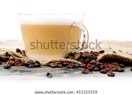 Photo of glass cup with coffee and beans on jute with white space - stock photo