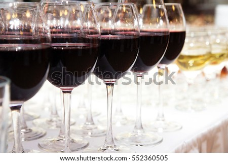 photo of Glasses of red wine on white table closeup