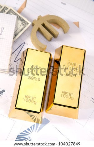 Photo of gold bars on graphs and statistics, studio shots, closeup