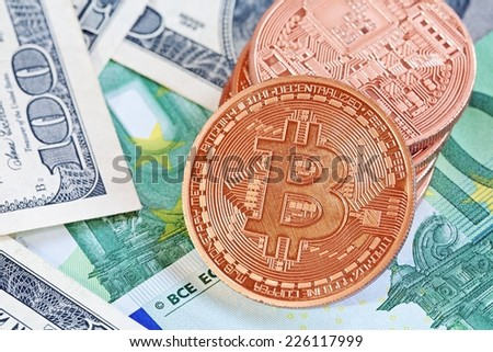 photo of golden bitcoins (new virtual currency) with traditional dollars and euro as a background - stock photo