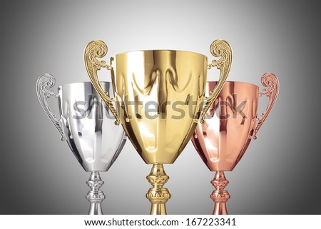 Photo of golden,silver and bronze trophies on gray background - stock photo