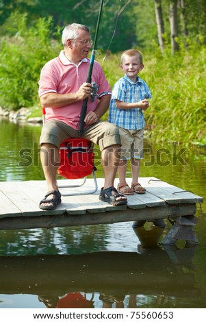 Photo of grandfather and grandson fishing in natural environment - stock photo