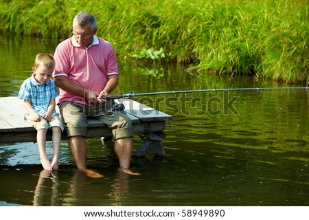 Photo of grandfather and grandson sitting on pontoon with their feet in water and fishing on weekend - stock photo