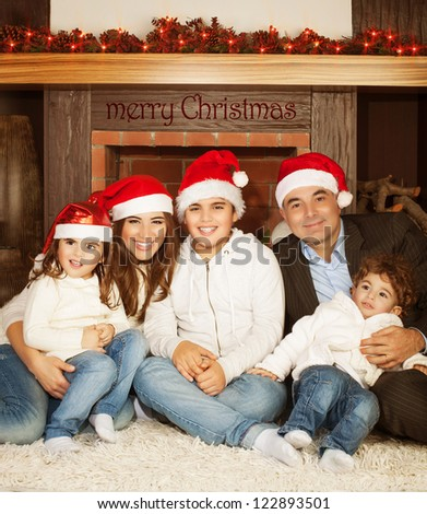 Photo of great happy family sitting near fireplace at home in Christmas eve, children with parents wearing red Santa Claus hat, enjoying winter holidays, New Year event, happiness and love concept - stock photo