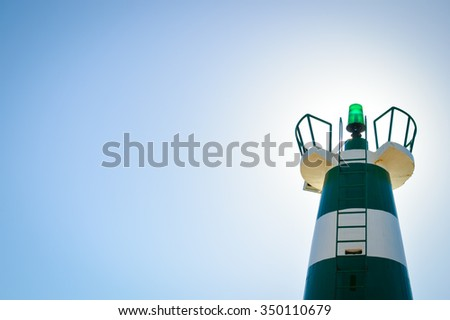 Photo of green and white striped lighthouse top with green lantern on blue clear sky with sunlight background  - stock photo