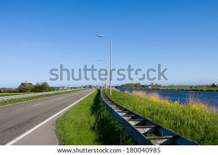 photo of green dike and road - stock photo