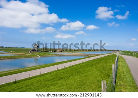 photo of green dike in wide open landscape  - stock photo