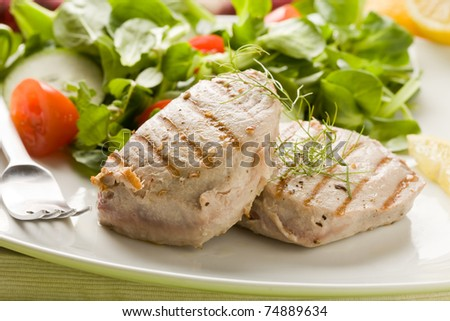 photo of grilled tuna steak with sald on green wooden table - stock photo