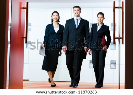Photo of group of business partners standing in front of open doors and going to enter conference hall - stock photo