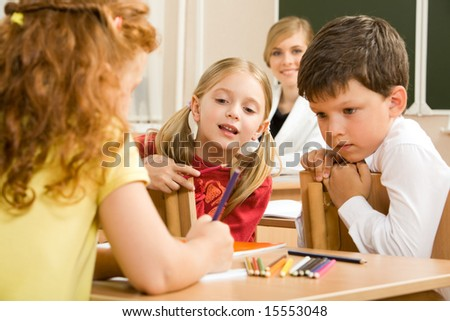 Photo of group of children sitting at the lesson and looking what their classmate drawing in her copybook - stock photo