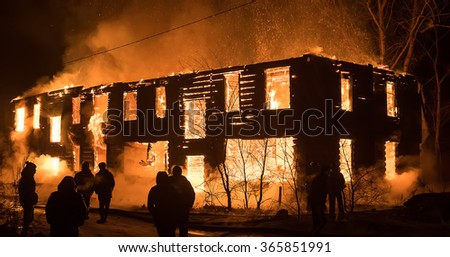 Photo of Group of People Looking at House on Fire. Big Old Wood House on Fire. Fire Safety Concept - stock photo