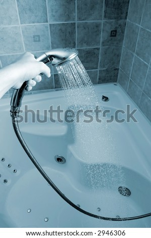 Photo of hand holding silver showerhead.
