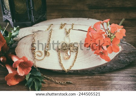 photo of handmade necklace over wooden table with flowers. retro style image, glamour and style concept - stock photo