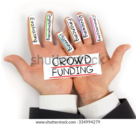 Photo of hands holding paper cards with CROWD FUNDING concept words - stock photo