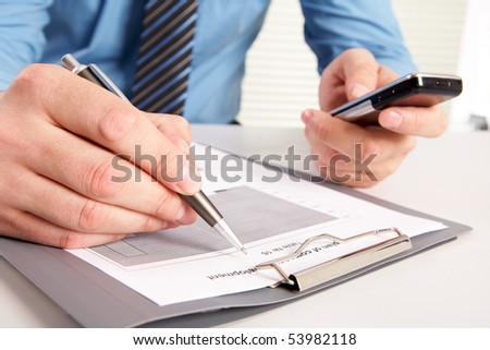 Photo of hands holding phone and pen over documents