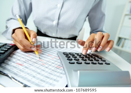 Photo of hands making notes with pencil and pressing calculator buttons - stock photo